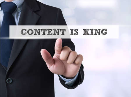 news values: CONTENT IS KING, Businessman touching a touch screen on blurred city background