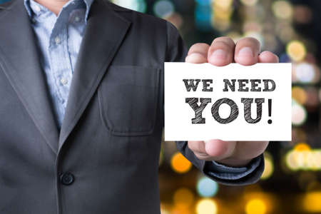 Businessman message on the card shown on blurred city background, holding WE NEED YOU! Stock Photo