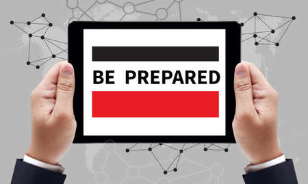 formulate: BE PREPARED text on the tablet pc screen held by businessman hands - online concept, top view