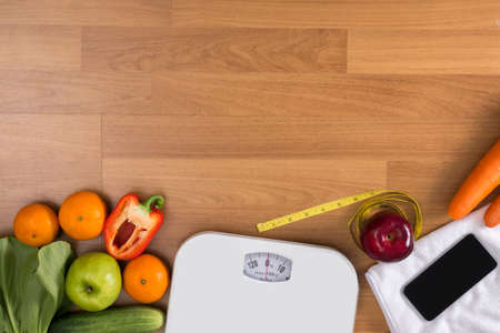 fat food: Fitness and weight loss concept, dumbbells, white scale, fruit and tape measure on a wooden table, top view, free copy space