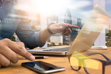 comercio: Recortada silueta del tiro de las manos de un hombre que usa una computadora portátil, joven estudiante masculino escribiendo en la computadora sentado en la mesa de madera, teléfono en la mesa, sol filtro