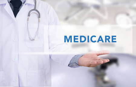 Health concept - MEDICARE on Medical Doctor holding hands Stock Photo