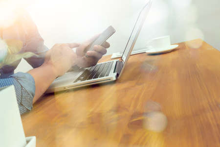 success business: designer hand working and smart phone and laptop on wooden desk in office Stock Photo