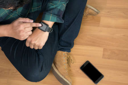 angle bar: Young stylish man checking his smartwatch in cafe bar. High angle shot. Toned image.