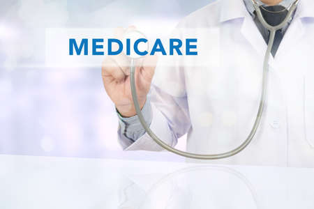 Medicine doctor hand working, Health concept - MEDICARE sign virtual screen Stock Photo
