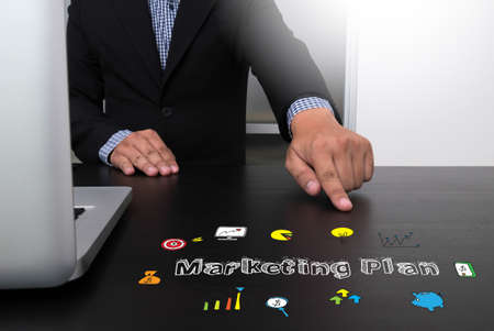 Business team hands at work with financial reports and a laptop, top view Marketing Plan