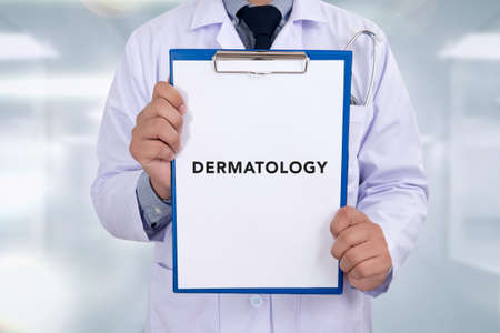 doctor writing: DERMATOLOGY message on Professional doctor writing medical records on a clipboard Stock Photo