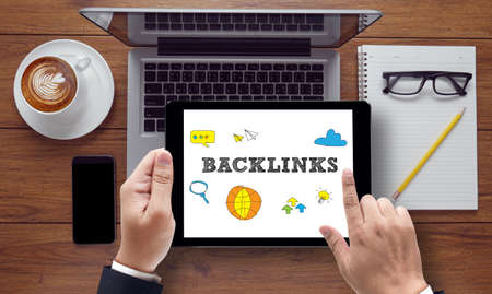 backlinks: Backlinks Technology  Web Concept on the tablet pc screen held by businessman hands - online, top view Stock Photo