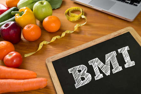 BMI body mass index formula rate formula in a board, fruit and tape measure on a wooden table, top view, Blank board copy space Stock Photo