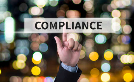 categorized: Compliance Concept, Business man with hand pressing a button on blurred abstract background