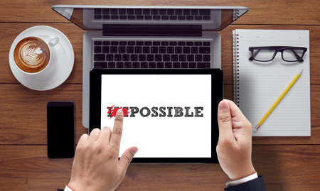 Impossible concept on the tablet pc screen held by businessman hands - online, top view Stock Photo
