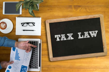 tax law: Businessman working at office desk and using computer and objects, coffee, top view, TAX LAW  concept