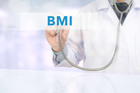 excess: BMI body mass index Close up of a male doctor in scrubs using digital tablet.