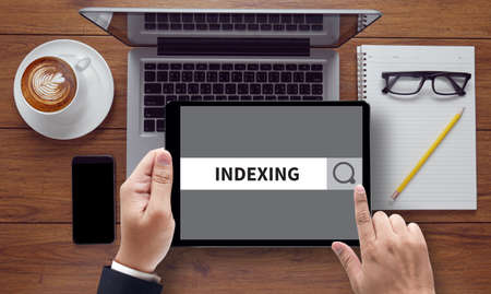 indexing: INDEXING CONCEPT on the tablet pc screen held by businessman hands - online, top view