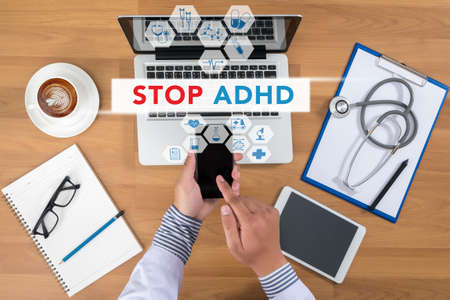adhd: STOP ADHD Doctor working at office desk and using a mobile touch screen phone, computer and medical equipment all around, top view, coffee Stock Photo