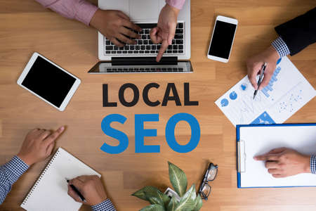 Local SEO Concep Business team hands at work with financial reports and a laptop, top view Stok Fotoğraf - 54129634