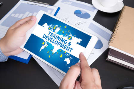 doing business: TRAINING & DEVELOPMENT CONCEPT, Modern people doing business, graphs and charts being demonstrated on the screen of a touch-pad,
