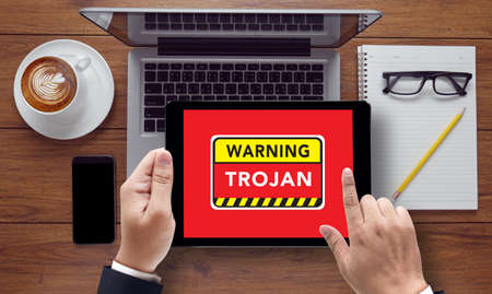 malicious software: Warning Trojan Concept , on the tablet pc screen held by businessman hands - online, top view Stock Photo