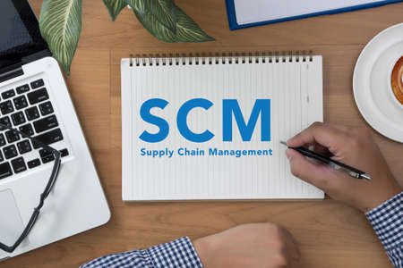 scm: SCM Supply Chain Management concept man hand notebook and other office equipment such as computer keyboard, digital tablet, pencil, mug of coffee and glasses on wooden office desk. Stock Photo