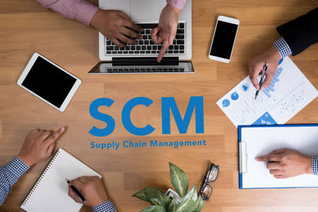scm: SCM Supply Chain Management concept Business team hands at work with financial reports and a laptop, top view