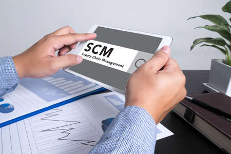 scm: SCM Supply Chain Management concept man using tablet computer, Marketing data paper3 Stock Photo