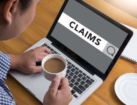 claims: CLAIMS CONCEPT Businessman at work. Close-up top view of man working on laptop while sitting at the wooden desk , coffee Stock Photo