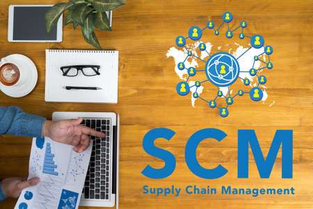 scm: SCM Supply Chain Management concept Businessman working at office desk and using computer and objects, coffee, top view, with copy space