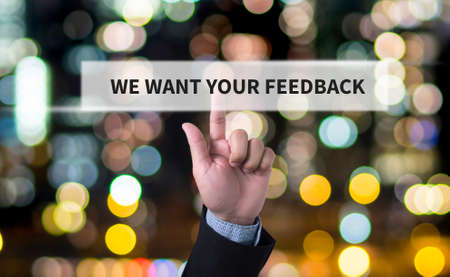 WE WANT YOUR FEEDBACK Concept Business man with hand pressing a button on blurred abstract background
