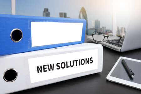 new solutions: NEW SOLUTIONS Office folder on Desktop on table with Office Supplies. Stock Photo