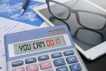 sayings: YOU CAN DO IT Calculator  on table with Office Supplies.