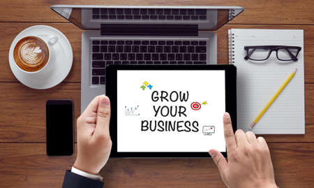 GROW YOUR BUSINESS CONCEPT , on the tablet pc screen held by businessman hands - online, top view