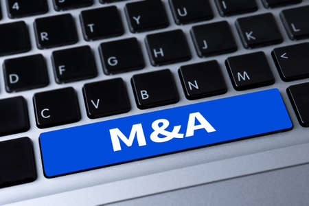 mergers: M&A (MERGERS AND ACQUISITIONS) a message on keyboard Stock Photo