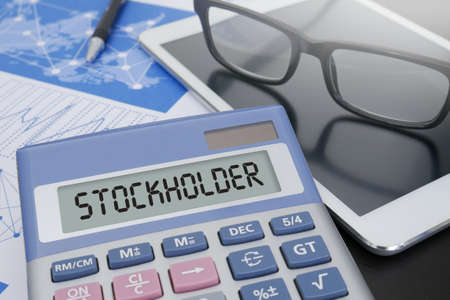 stockholder: STOCKHOLDER CONCEPT Calculator  on table with Office Supplies. Stock Photo