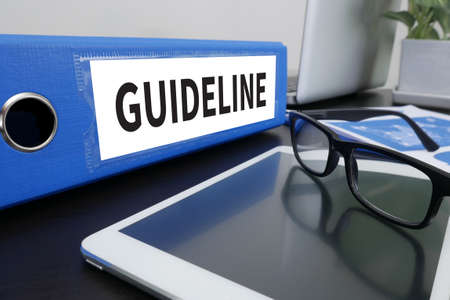 guideline: GUIDELINE Office folder on Desktop on table with Office Supplies. Stock Photo