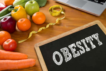 childhood obesity: OBESITY Fitness and weight loss concept, fruit and tape measure on a wooden table, top view,