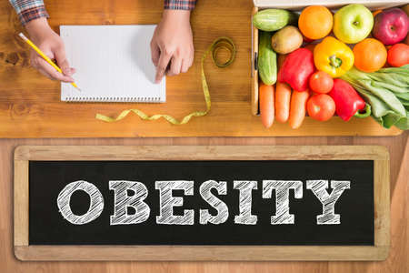 childhood obesity: OBESITY notebook with fresh vegetables and  on a wooden table, Stock Photo
