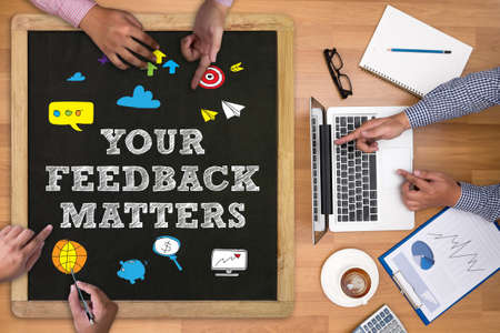 solicitation: YOUR FEEDBACK MATTERS Businessman working at office desk and using computer and objects on the right, coffee,  top view,