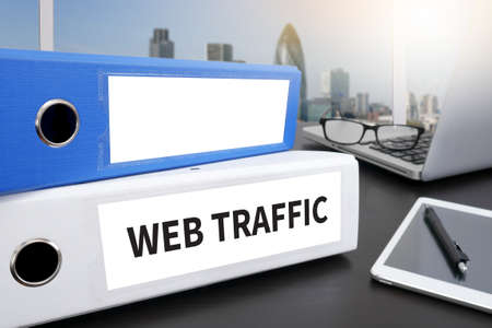 web traffic: WEB TRAFFIC Office folder on Desktop on table with Office Supplies. Stock Photo