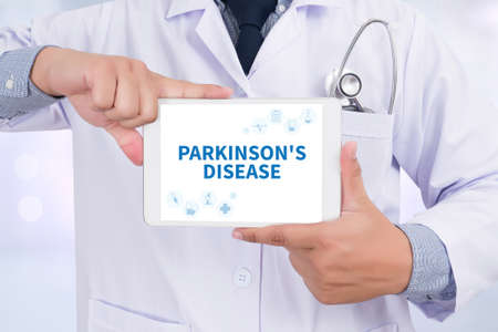 motor neuron: PARKINSONS DISEASE Doctor holding  digital tablet Stock Photo