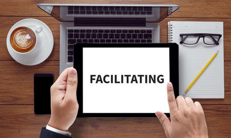 facilitator: FACILITATING , on the tablet pc screen held by businessman hands - online, top view Stock Photo