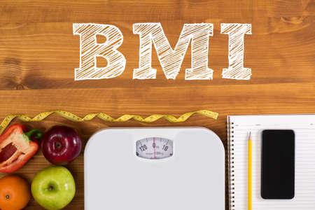 bovenaanzicht, fitness en gewichtsverlies concept, dumbbells, witte schaal, handdoeken, fruit, BMI body mass index formule rate formule in een raad