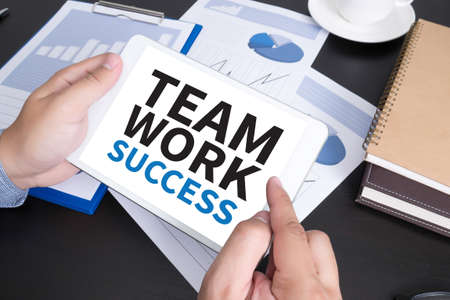 doing business: TEAMWORK SUCCESS CONCEPT Modern people doing business, graphs and charts and touch-pad