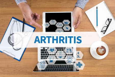 arthritic: ARTHRITIS Doctor touch digital tablet, desktop with medical equipment on background, top view, coffee