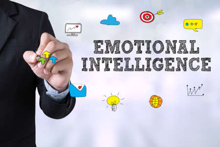 EMOTIONAL INTELLIGENCE Businessman drawing Landing Page on blurred abstract background Stock Photo