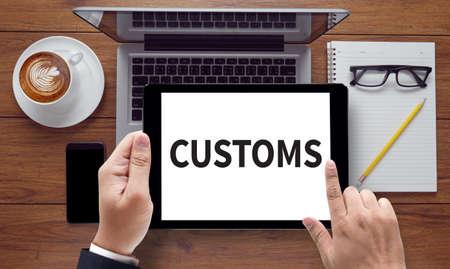 DOUANES, sur l'écran de la tablette pc tenue par des mains d'homme d'affaires - en ligne, vue de dessus