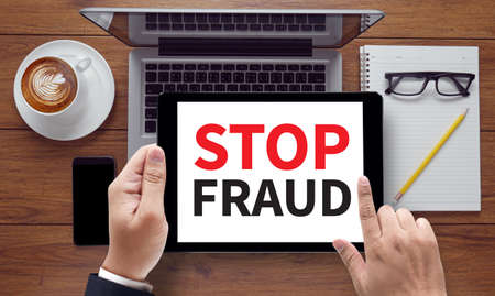 corrupt: STOP FRAUD, on the tablet pc screen held by businessman hands - online, top view Stock Photo