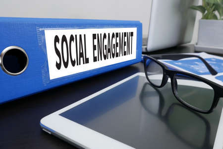 involving: SOCIAL ENGAGEMENT Office folder on Desktop on table with Office Supplies. ipad