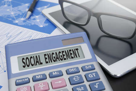 participatory: SOCIAL ENGAGEMENT Calculator  on table with Office Supplies. ipad Stock Photo