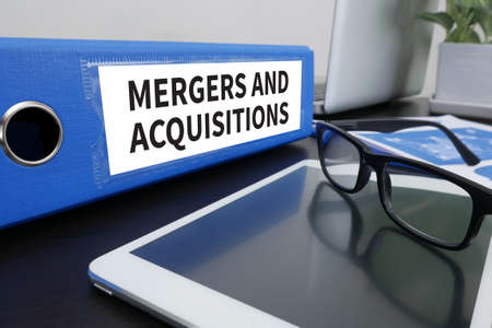mergers: M&A (MERGERS AND ACQUISITIONS) Office folder on Desktop on table with Office Supplies. ipad