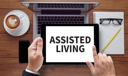 assisted living: ASSISTED LIVING Doctor touch digital tablet, desktop with medical equipment on background, top view, coffee, on the tablet pc screen held by businessman hands - online, top view